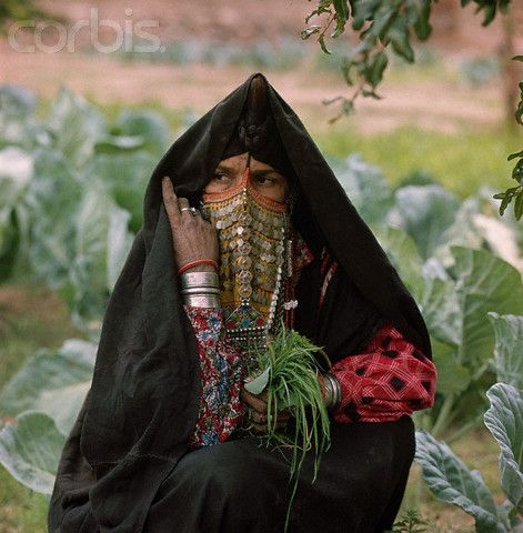 Africa | A Bedouin woman in a garden wears a black burka, a face veil covered with embroidery and dangling bits of metal, along with silver bracelets and rings. She holds a bunch of freshly picked grass and herbs. Wadi Feran, Sinai, Egypt.  1962. | © Roger Wood
