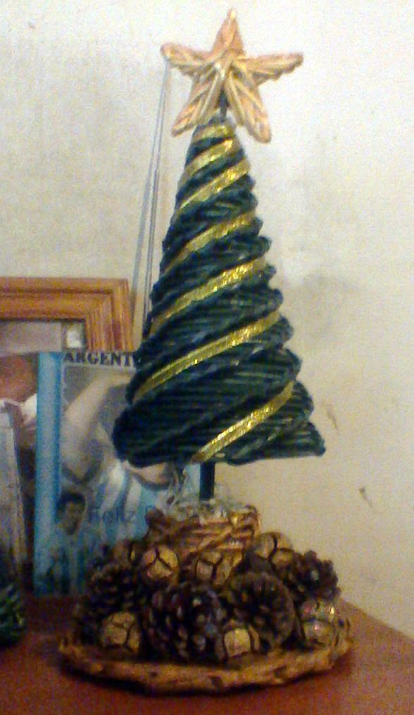Árbol de Navidad sobre una base redonda, con piñas y semillas naturales.