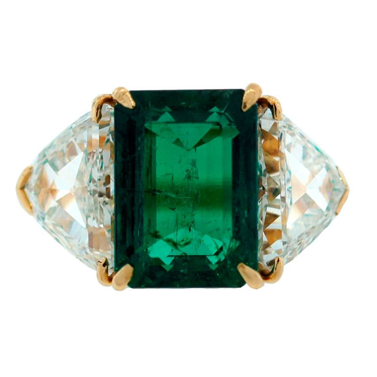 Harry Winston Colombian Emerald (Gubelin Cert) Diamond Yellow Gold Ring. Timeless and classy three-stone ring created by Harry Winston in 1968. Features a 3.58-ct Colombian emerald flanked by a pair of trillion cut diamonds (total weight 2.36 carats) mounted in 18k yellow gold. The emerald is accompanied by a gemological report from Gubelin lab, which states that the emerald is of Colombian origin. c 1968