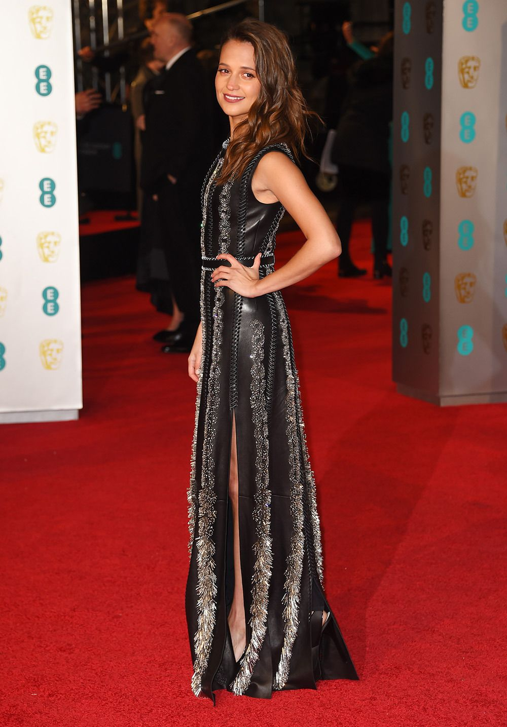 licia Vikander Con un vestido embellecido sobre cuero con abertura de Louis Vuitton.