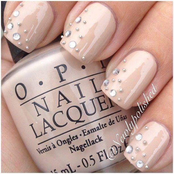elegante manicura con uas en color beige decoradas con perlitas plateadas y perlas cristalinas