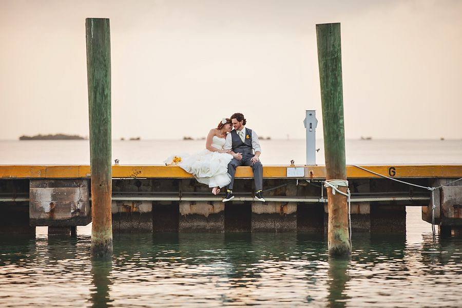 Here's to our first year, and many more to come! Wedding photo, sitting on a dock, barefoot, sunset, beach wedding, photos by jewel