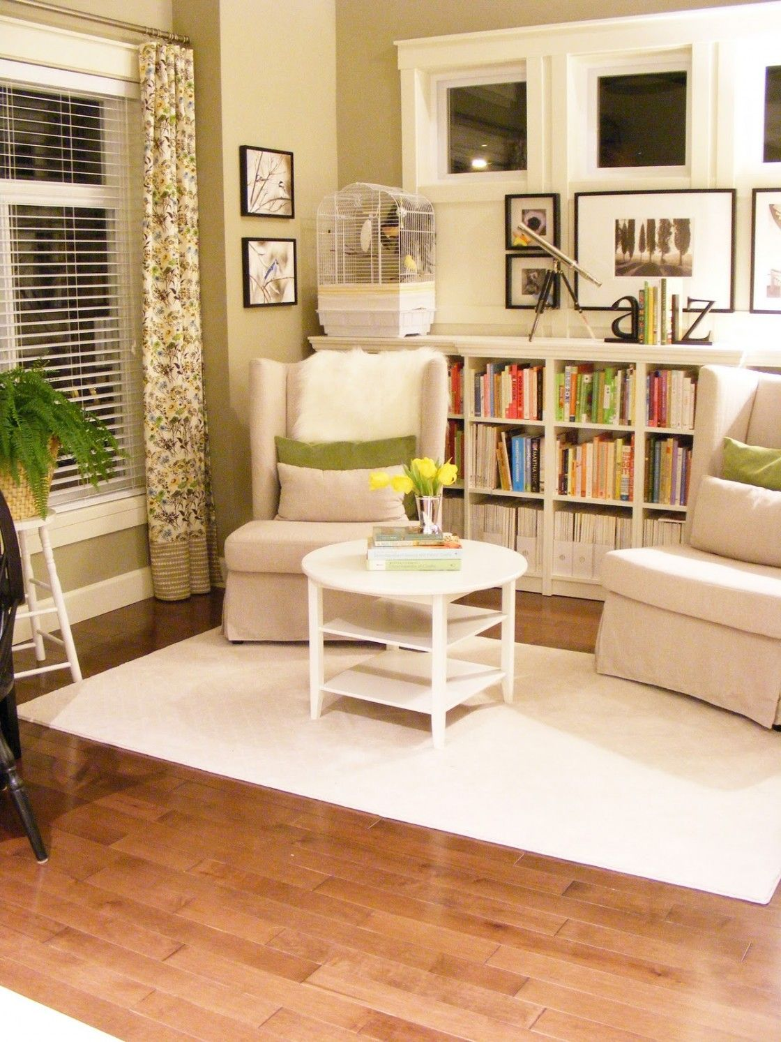 Small Home Library Design With Beautiful Pinch Pleat Florals Curtains And Mini White Finish Wooden Storage