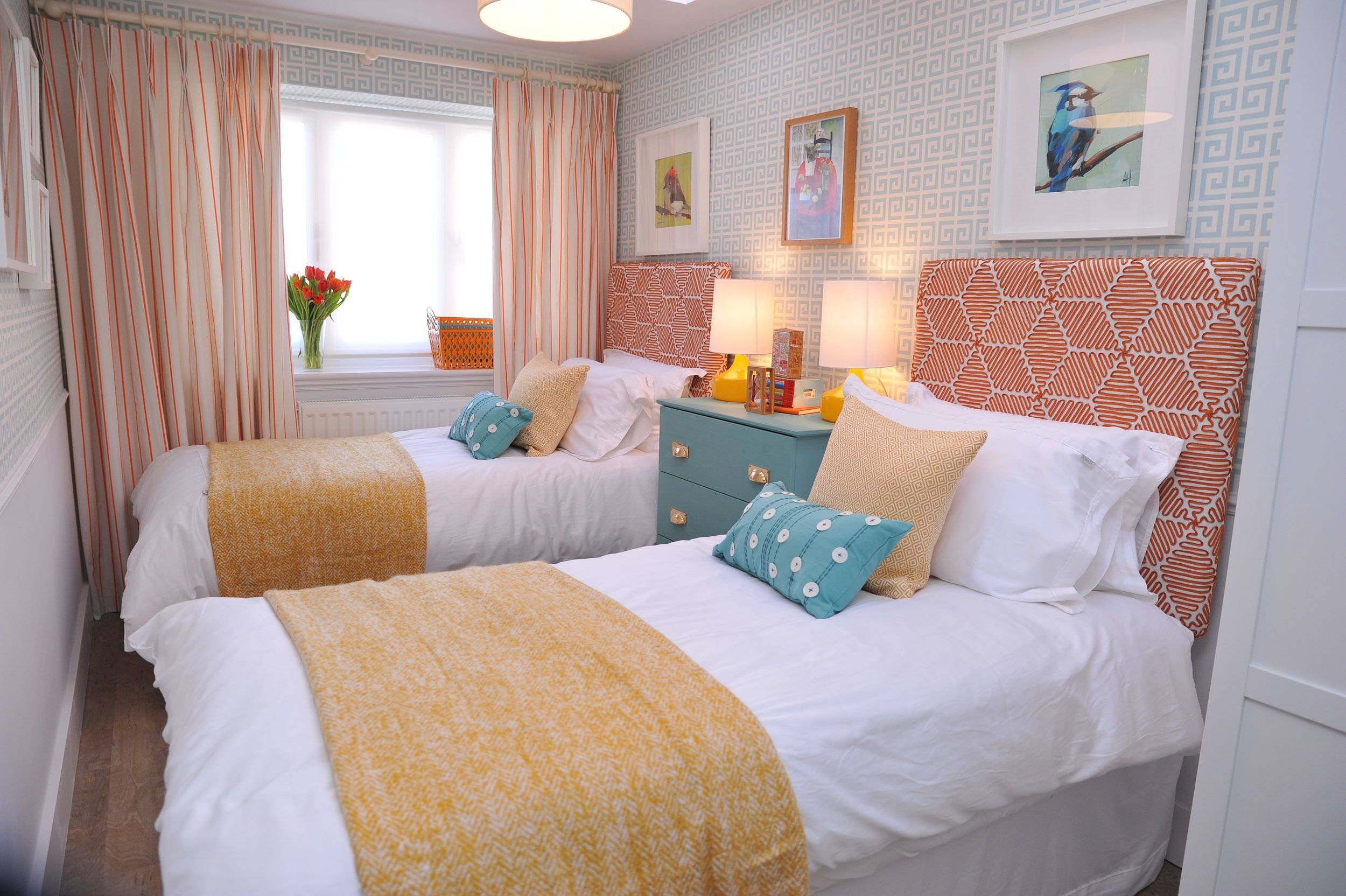 Twin bedroom with a blue geometric wallpaper and orange