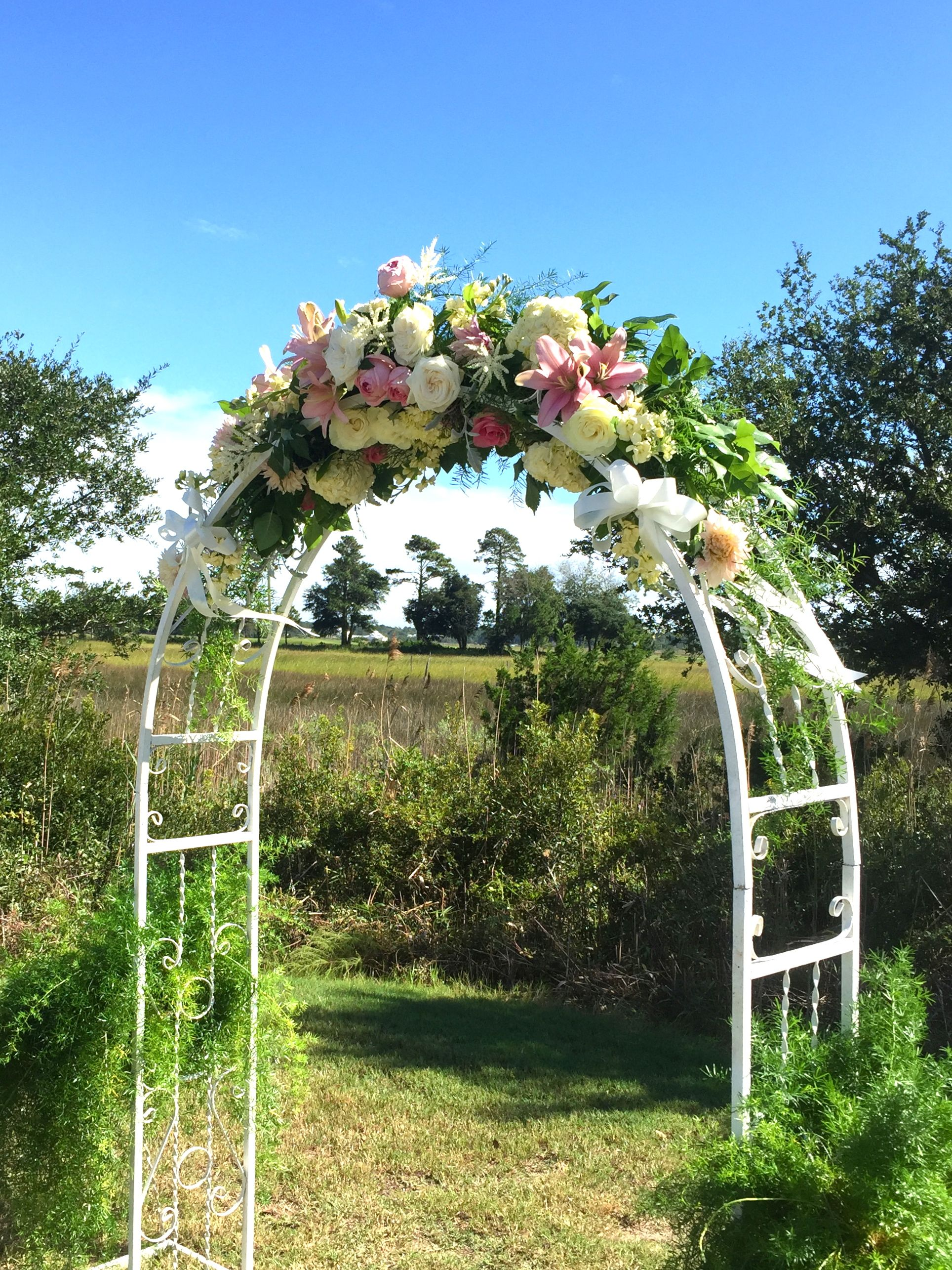 White Metal Arbor Decorated With Spray Of Flowers For A Wedding By Brunswick Town Florist In Southport Nc