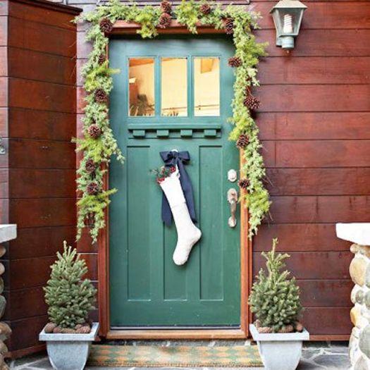 Ramas de pino o su imitación alrededor de la puerta luce muy bien. Puedendejarlas solo de la mitad hacia arriba de la puerta o completamente por todo el contorno