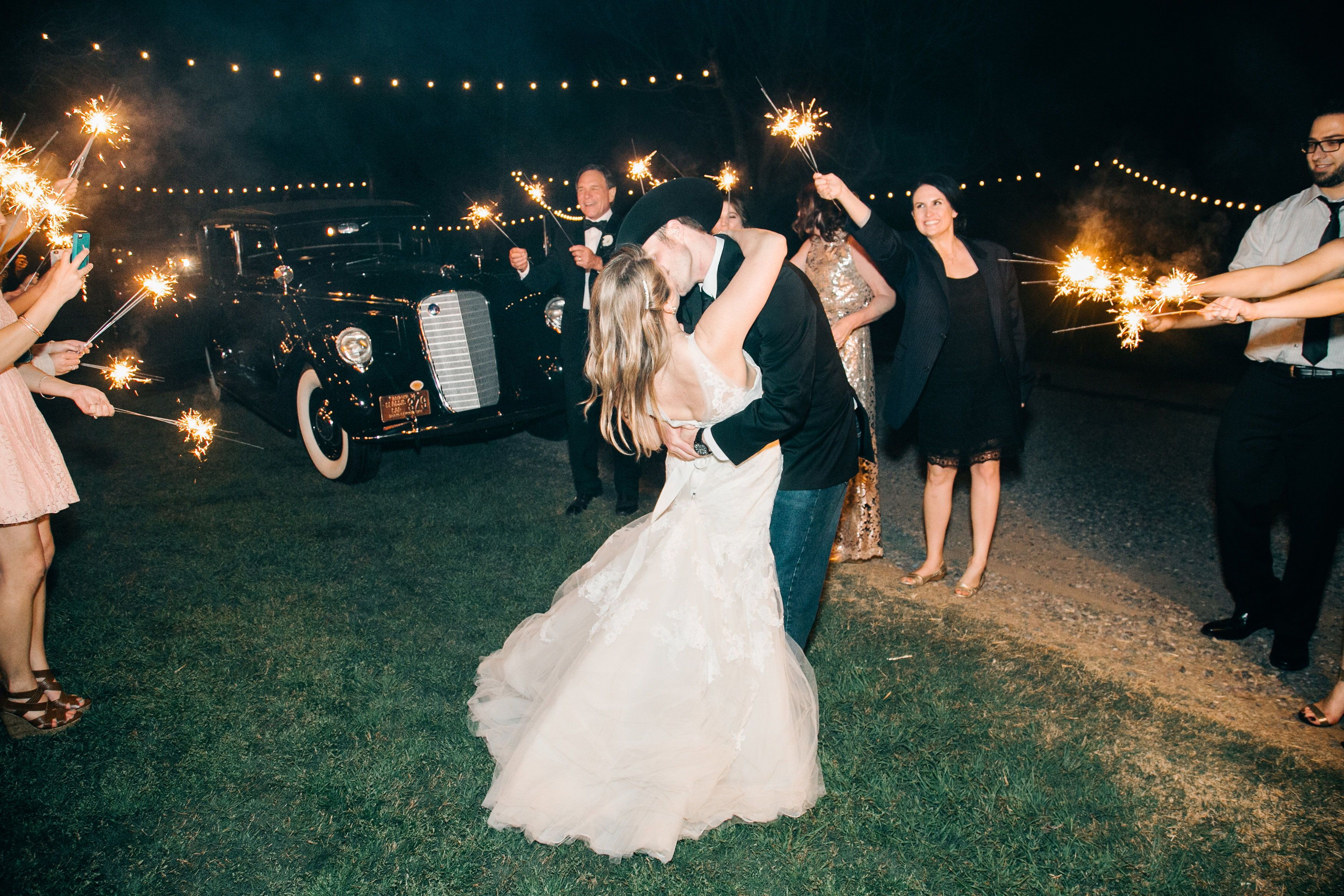 Kissing Couple With A Wedding Sparkler Exit By A Fancy Getaway Car Sparkler Exit Wedding Wedding Sparklers Sparklers