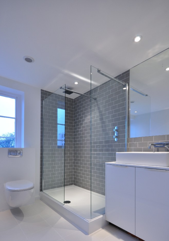 this bathroom uses grey metro tiles to make a fantastic feature of the walk in