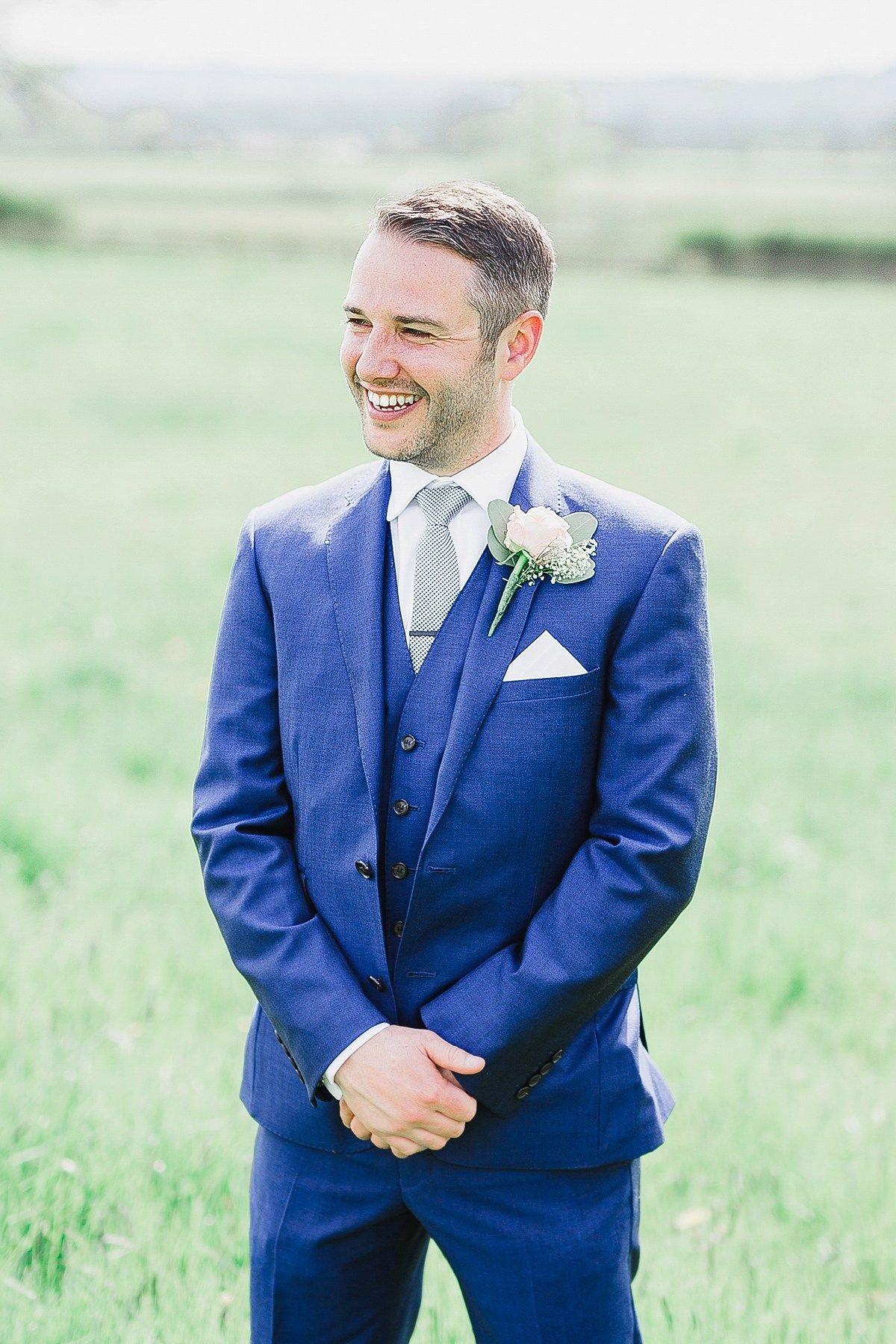 Groom wears a three piece blue suit. Photography by http://whitestagweddings.com/Photography.