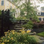 A flat stone staircase and lots of greenery help make this home more inviting and natural.