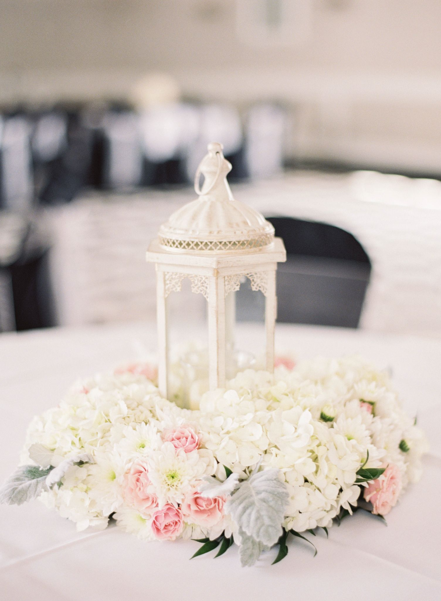 Ivory Lanterns With A Wreath Of Fresh White Hydrangea And Cushion Mums Pink Roses Dusty Miller Centerpieces