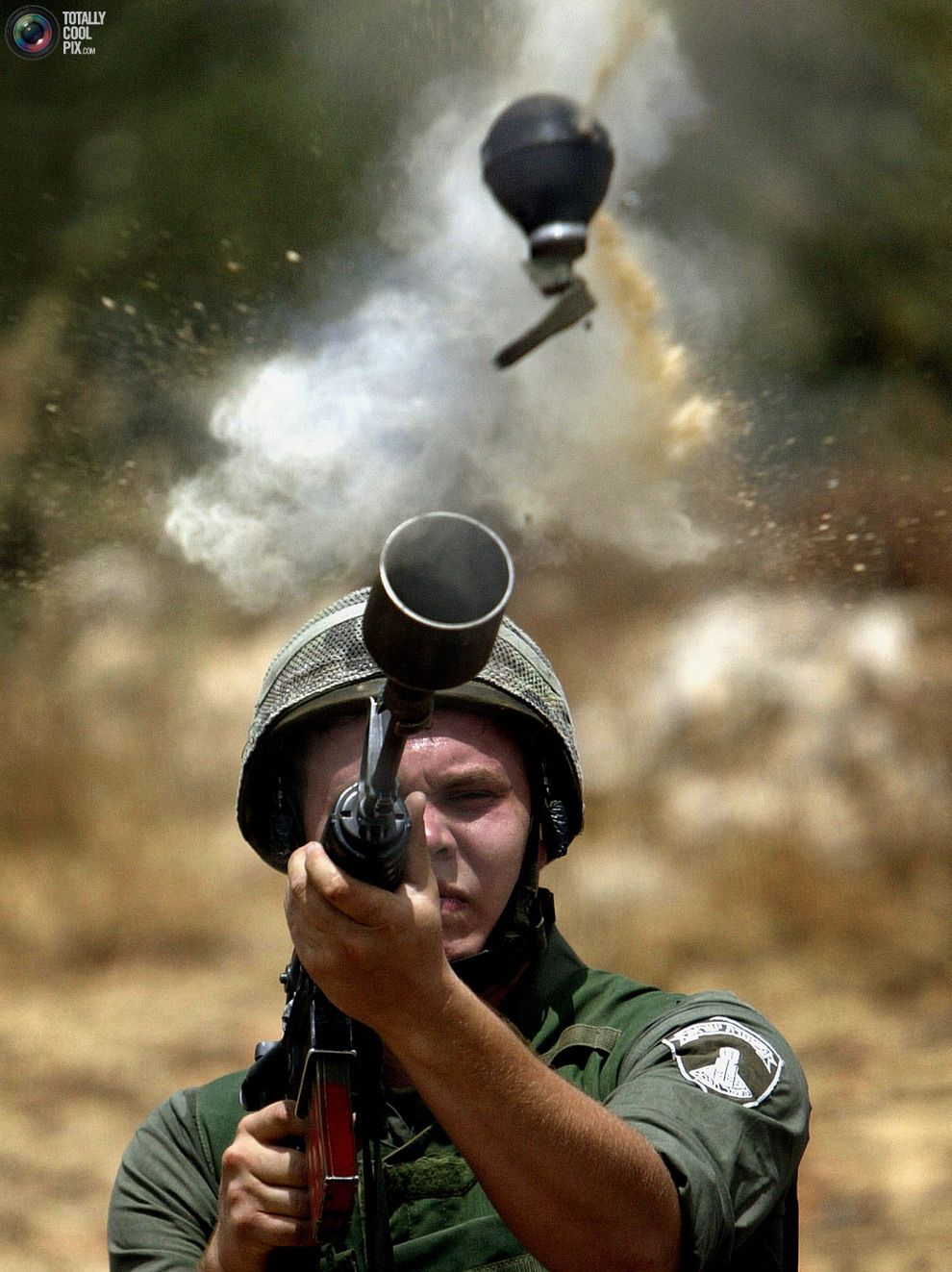 An Israeli border policeman fires teargas canister during a protest by Palestinians against the construction of the Israeli security barrier in the West Bank village of Az-Zawiya June 20, 2004.