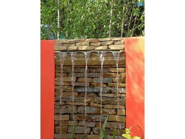 На фото оригинальный садовый фонтан. Он создан из камней, которые имеют разную форму, но ровную поверхность. Они выложенные в виде стенки, на верху которой течет вода и спадает вниз.