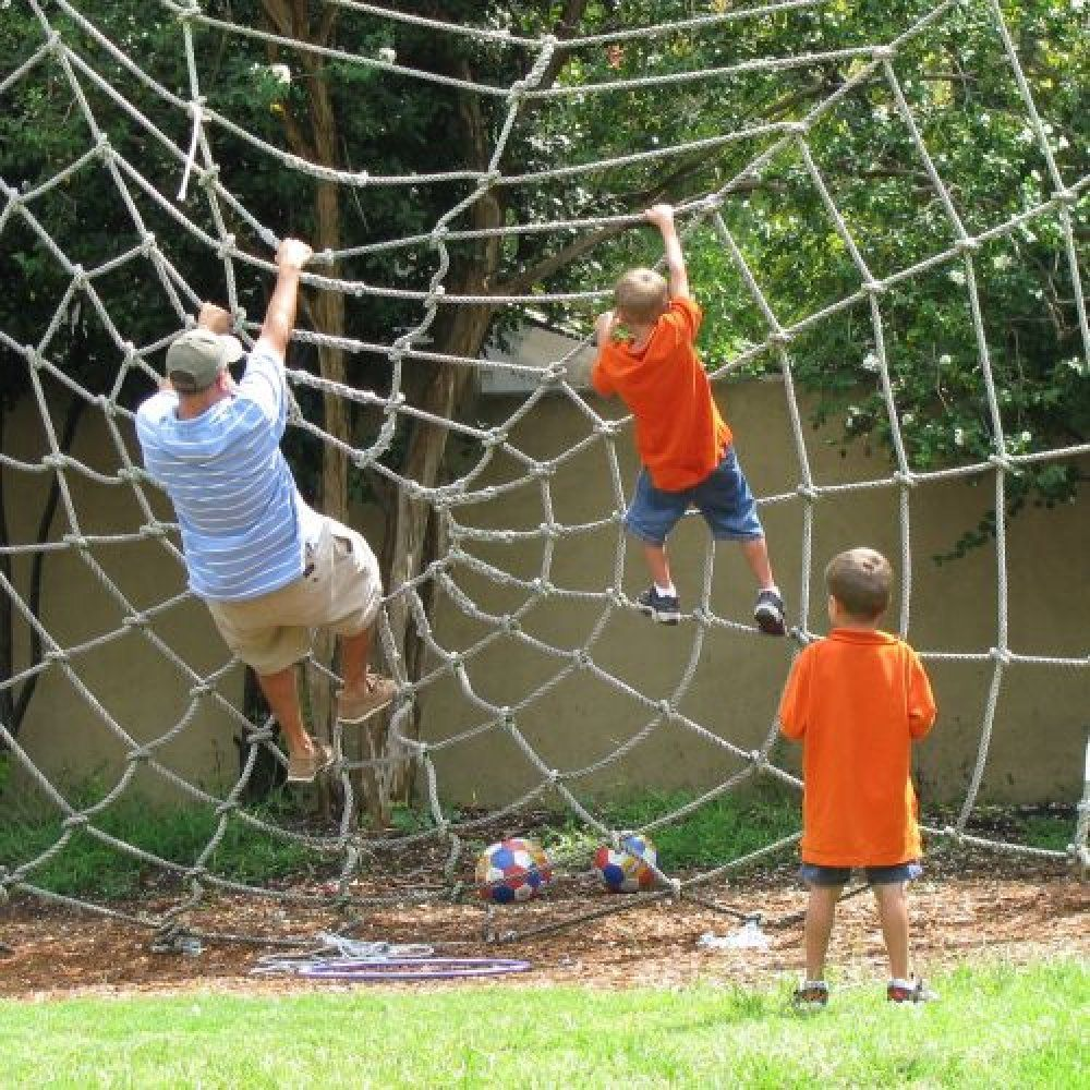 this backyard playground has a spider web net to climb
