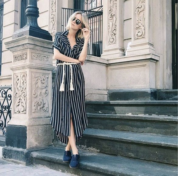 A Faithful the Brand dress is paired with flats and black sunglasses.