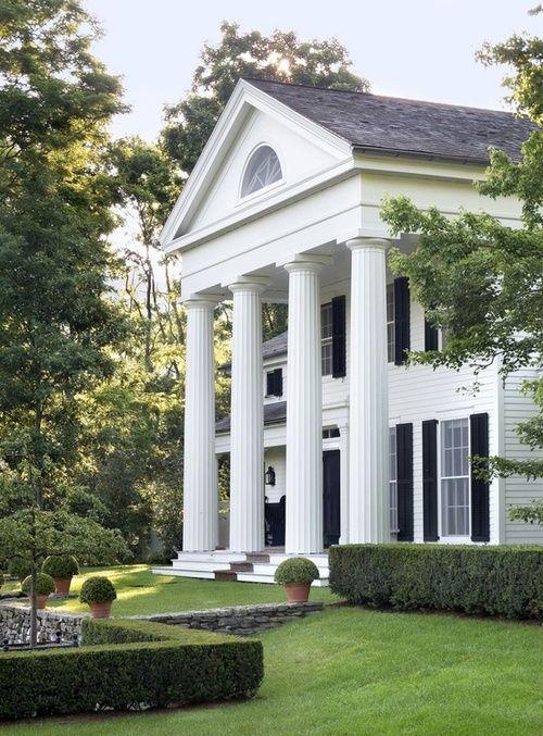 La maison est blanche avec des volets noirs et une porte noire, avec