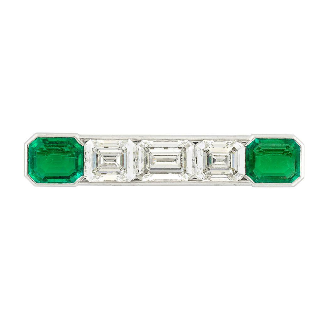 Platinum, Diamond and Emerald Brooch Centering three emerald-cut diamonds approximately 8.00 cts., tipped by 2 cut-cornered emerald-cut emeralds approximately 3.70 cts., approximately 6.8 dwts.