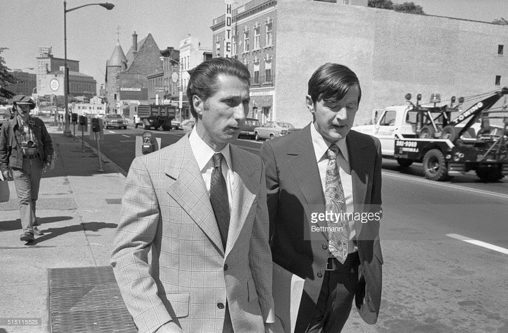 """Louis Anthony """"Bobby"""" Manna (born December 2, 1929 in Hoboken, New Jersey), is a New Jersey mobster and former consigliere of the Genovese crime family. Here he enters Mercer County Courthouse in Trenton with his attorney, Don Conway. Manna has spent three years in prison on contempt charges for refusing to testify about organized crime. Manna's motion for release was turned down and he was ordered back to jail. 1975."""