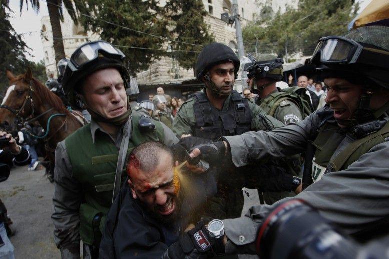 Funcionarios fronterizos israelíes arrojan spray de pimienta a un manifestante palestino herido durante los enfrentamientos en el Día de la Tierra . El día de la Tierra conmemora la muerte de seis árabes, asesinados por las fuerzas de seguridad en 1976 durante las protestas contra los planes del gobierno de confiscar tierras en la región norte de Israel Galilea. Foto: Ammar Awad.