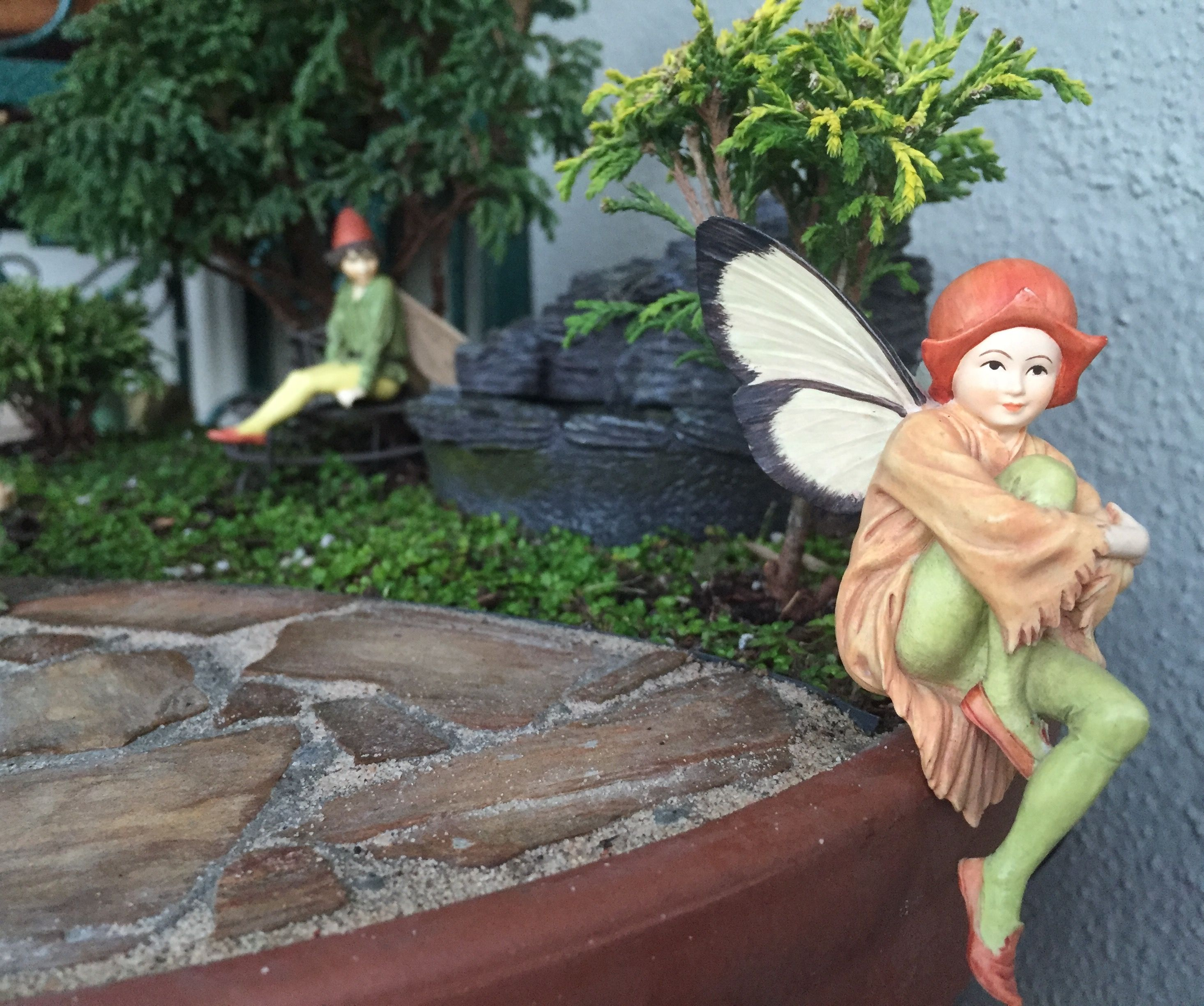 Miniature Fairy Garden - FOUNTAIN OF FAIRIES has two scenes going on; has a shale water fountain and flagstone patio. Scene one is about a boy fairy who has his eyes on a girl fairy who seems to be enjoying some fresh air. 2/2016