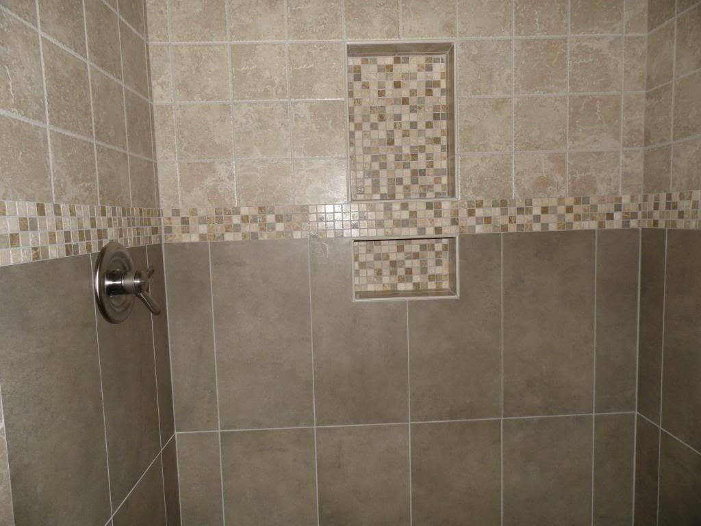 Two shelf shower niche with tumbled mosaic banner running through it
