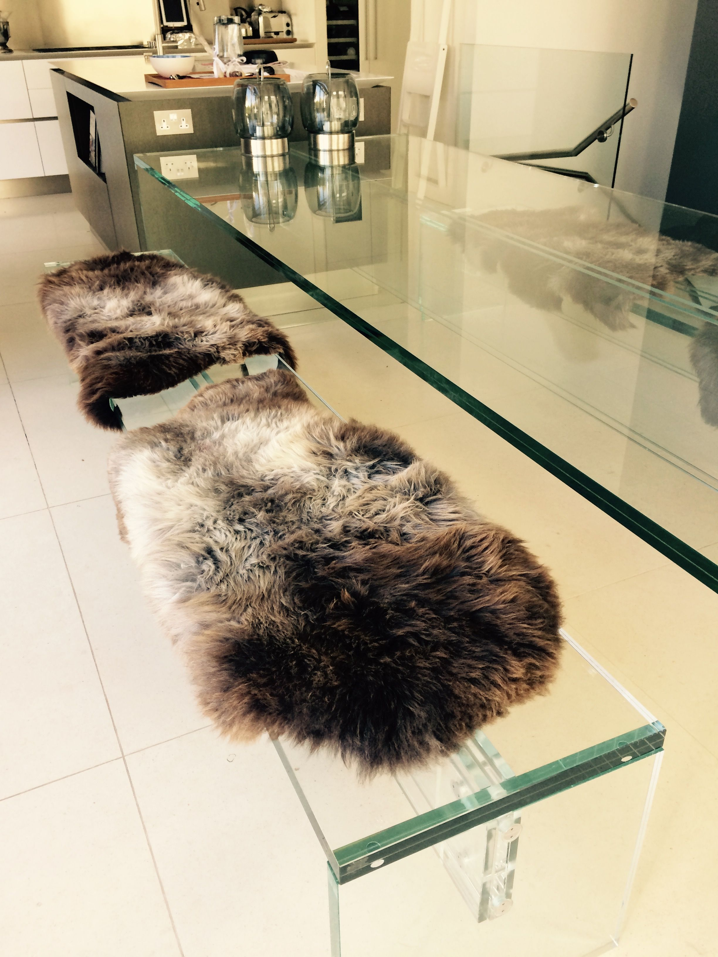 Two Rare Breed Sheepskins Make Great Dining Bench Covers In This Modern Area