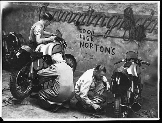 Mechanics work on two Norton motorcycles before the start of the Tourist Trophy Race on the Isle of Man