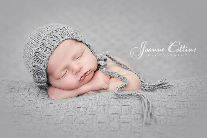 Newborn photography kent newborn baby photographed wearing very ute grey hat asleep resting on arms