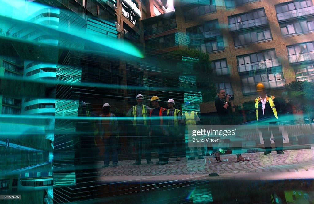 Workmen are seen waiting to install sculptures entitled 'Lock Level Line' at regenerated Paddington Basin, September 3, 2003 in London. The four sculptures made of glass and steel by Danny Lane were transported down the Grand Union canal from the artist's studio as part of an effort to regenerate Paddington Basin.