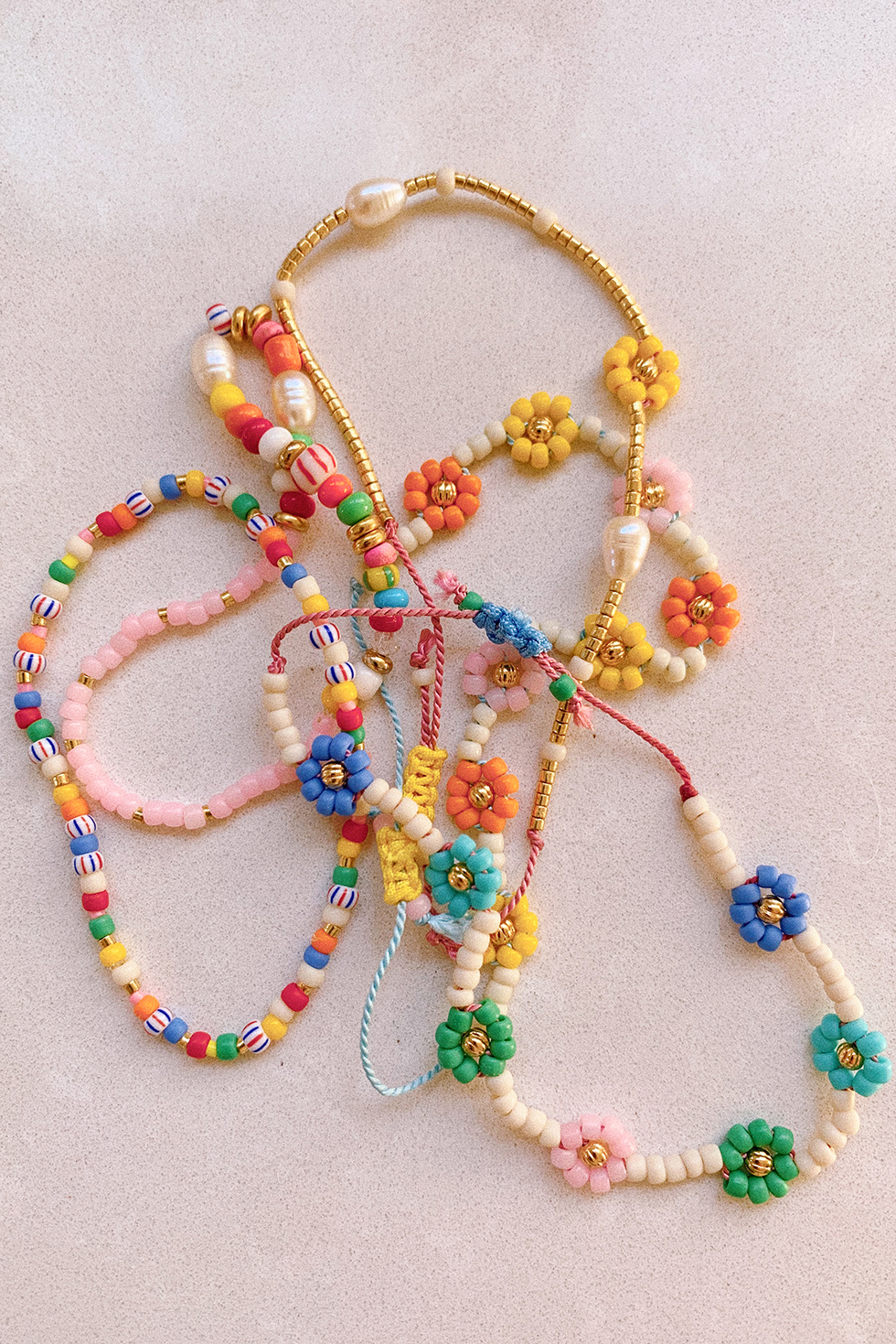 Honestly, is there anything happier than daisies?! I was desperately needing a dose of happy over the weekend and whipped up a few colorful bracelets to soothe the soul. Making daisy chains from seed beads…