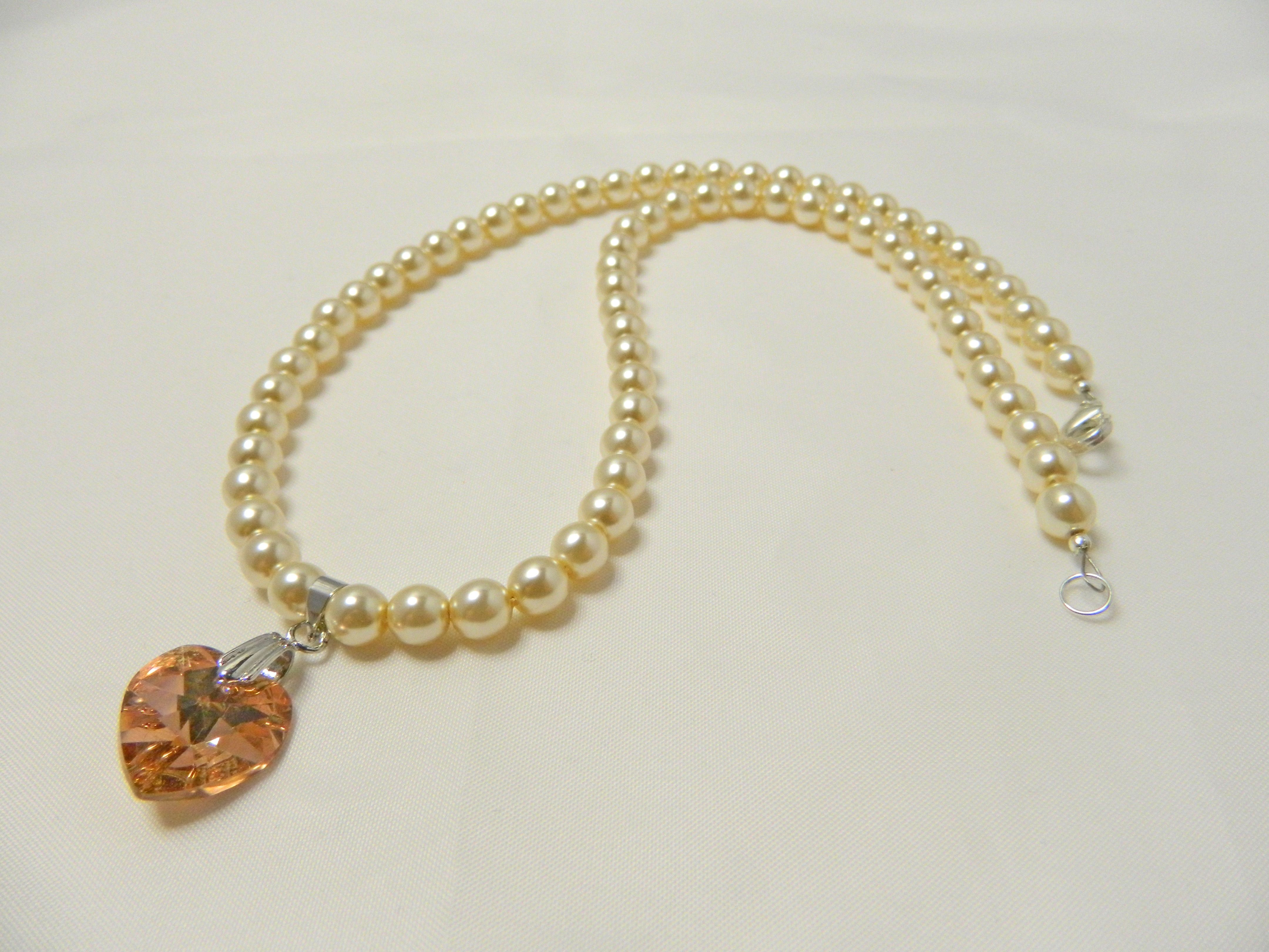6mm Preciosa Czech Glass Ivory pearls and 14mm Swarovski Golden Shadow Heart Crystal pendant necklace with trigger clasp.  Necklace length 18 inches.  Price £18