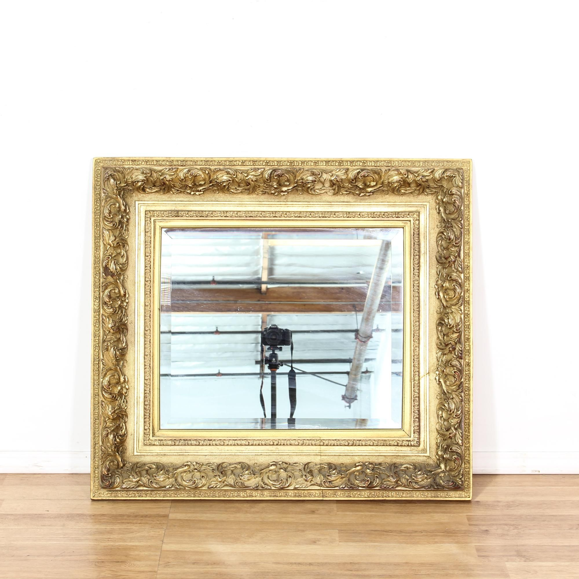 This ornate mirror is featured in a metal with a shiny antique gold ...