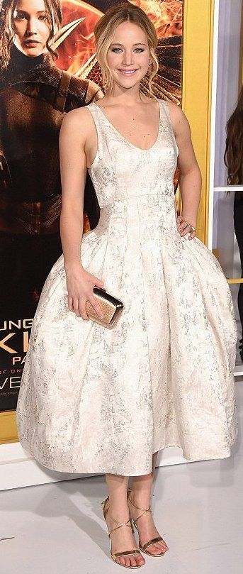 Jennifer Lawrence in silver jacquard silk pannier-style Dior Haute Couture tea-length dress that she styled with a rose gold Roger Vivier clutch, Vita Fede ear jackets, Repossi ear cuff, an Anita Ko ring, and gold Aquazzura sandals.  http://www.dailymail.co.uk/tvshowbiz/article-2838790/Girl-fire-Jennifer-Lawrence-looks-stopping-shimmering-ivory-gown-Hunger-Games-Mockingjay-1-LA-premiere.html