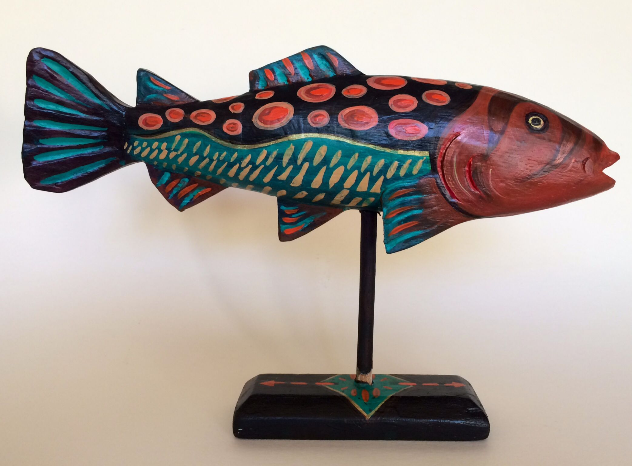 Coral Fish, Katy Bratun. Wood base, painted with acrylic paint. An easy fish form can be made with crumpled paper, smoothed over with flat paper and masking tape. Then paper mâché, about 3 or 4 layers. Then paint when it is dry with acrylic. Buttons or beads glued on for eyes...