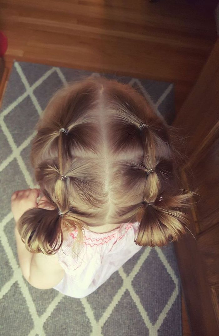 two-buns-blonde-hair-pink-top-cute-hairstyles-for-little-girls-grey-carpet-wooden-door