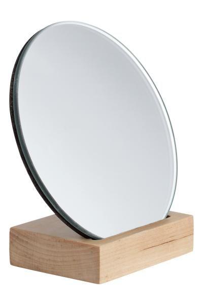 Een kleine, ronde spiegel. De voet en de achterkant zijn van hout ...