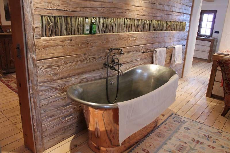 Freistehende Badewanne aus Messing in Altholz eingefasst Sie ist