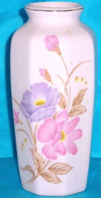 Octagonal shaped ceramic vase is a pale pink eight-sided vase measuring 6 inches high with 1 3/4 inch opening. Hallmark Japan with signature. The flowers appear hand painted, with pale purple large flower and darker pink flower with yellow centers and buds (perhaps peonies ). There are also a few yellow buds. Mid to late 20th Century pottery