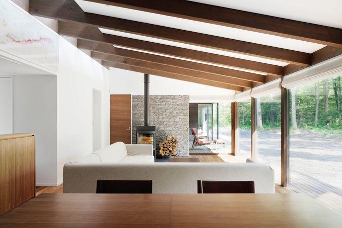 落ち着いた色使いのシックな空間です 登り梁が連続する天井がきれいです 梁と梁のあいだを白く仕上ることで 山小屋にならず モダンに仕立てています 薪ストーブの背面の石調