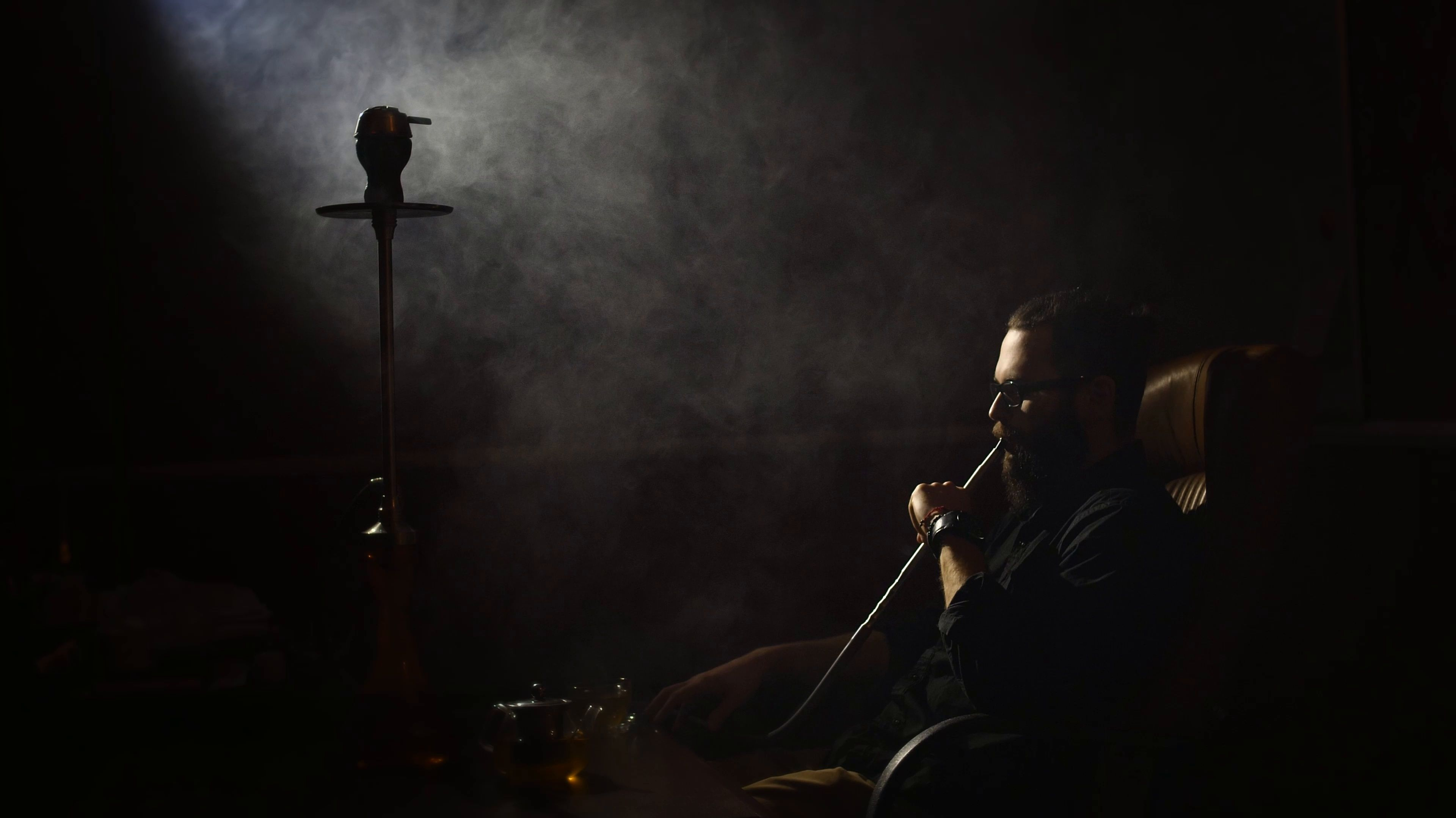 Young Bearded Man In Glasses Smokes A Hookah And Blow Out Smoke