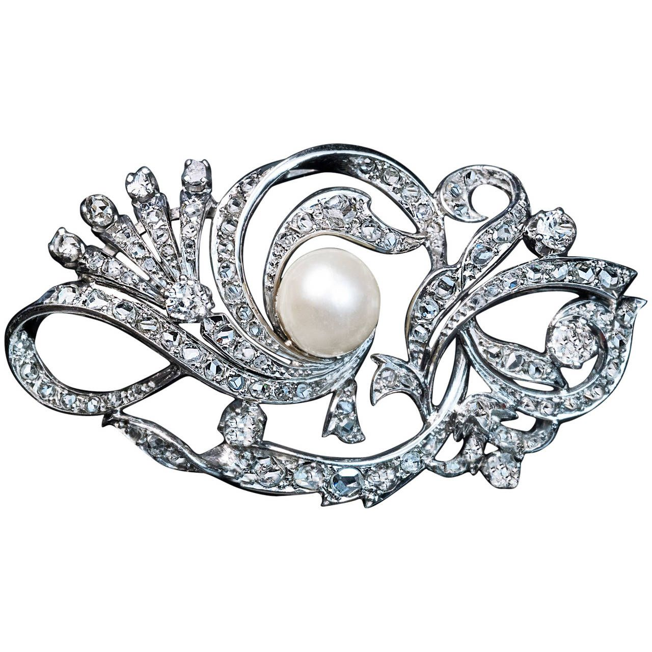 Pearl Diamond Platinum Brooch C1920. The brooch is designed as a stylized interlaced scrolling floral designs embellished with numerous old cut brilliant and rose diamonds and a 9 mm pearl. Estimated total diamond weight 3 carats