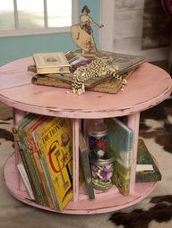 A littel pink paint helps turn an industrial wire spindle into a combination coffee table and book rack.