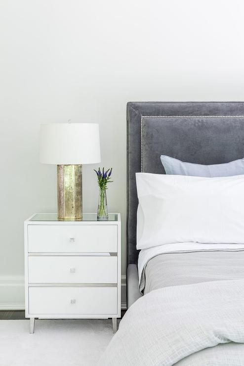 Gray Blue Velvet Headboard Sits On A Bed Dressed In White And Gray