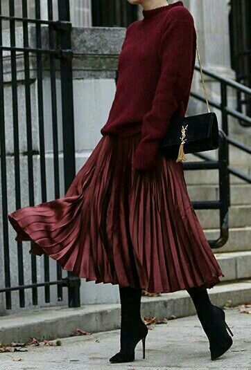 A cranberry pleated skirt with a big matching jeweled tone sweater, & high heele…