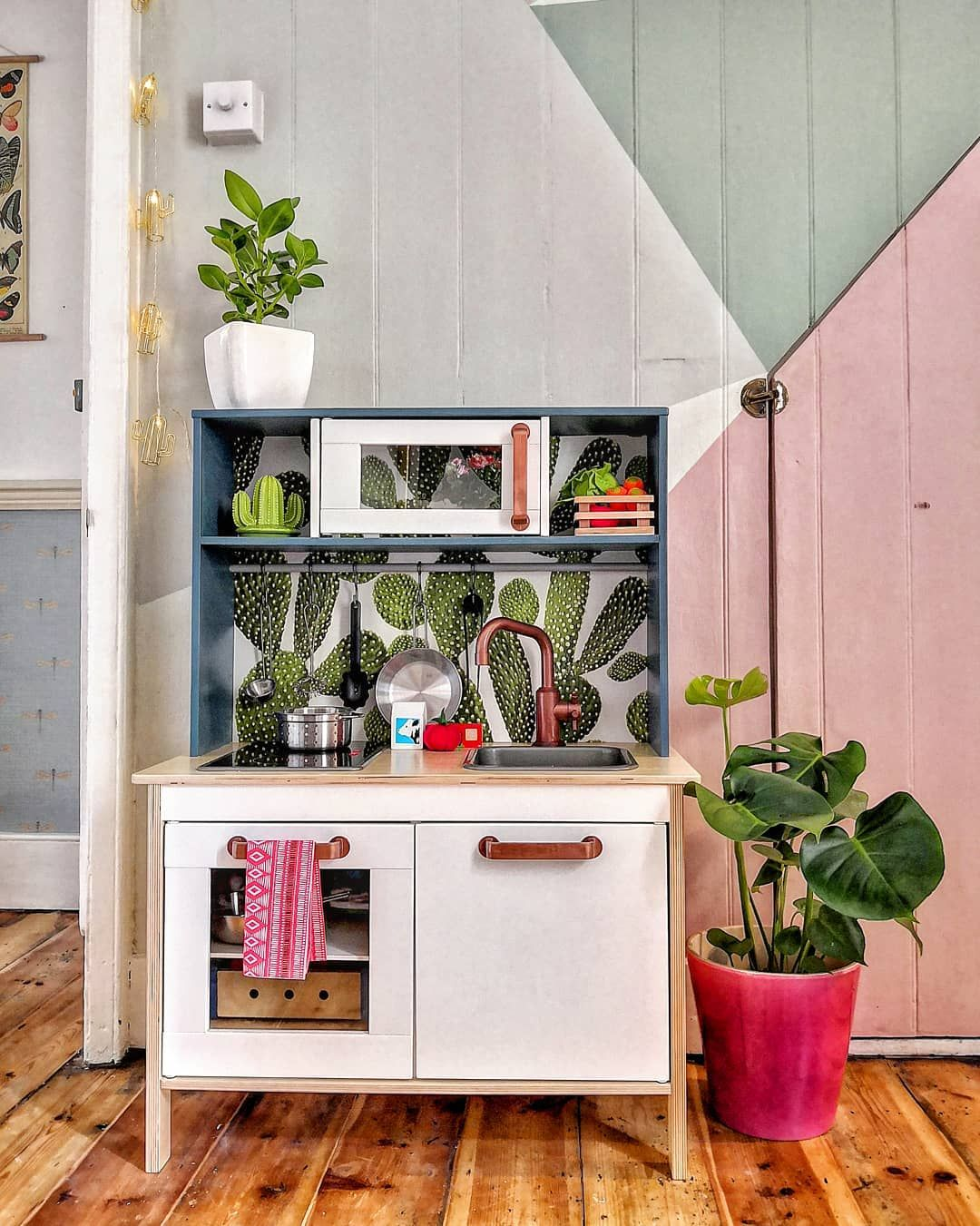 Ikea play kitchen hack with colourful wall backdrop behind
