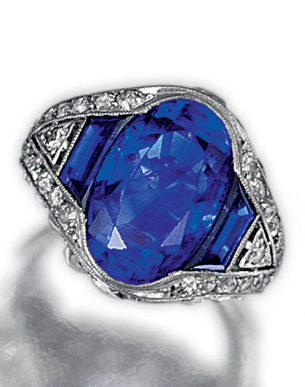 An Art Deco sapphire and diamond ring, circa 1925. Millegrain-set with an oval and two trapeze sapphires, within a border of circular-, single and rose-cut diamonds, mounted in platinum, French assay and maker's marks.