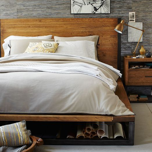 Lofted on an industrial-style iron base, the substantial Copenhagen Bed is made of solid wood that's been hand-planed to create a distressed look. Both rustic and refined, it has a grand presence.