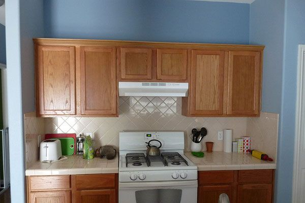 natural cabinets wood and light blue walls   kitchen with ...