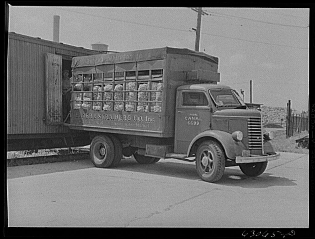 Loading potatoes onto truck from freight car. Chicago