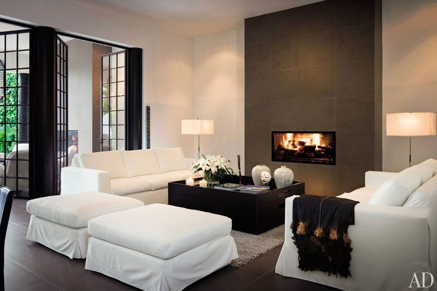 """For this minimalist residence in Mexico, designer Michael Schaible conceived interiors that are predominantly black and white, colors he says he finds """"so peaceful."""" Simple slipcovered sofas and ottomans surround the unornamented fireplace, which is cut into the wall. Noguchi floor lamps echo the hearth's shape. (September 2008)"""